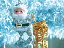 Liten leksak Santa Claus med gåvor på en briljant ljus silverbakgrund tonat Fotografering för Bildbyråer