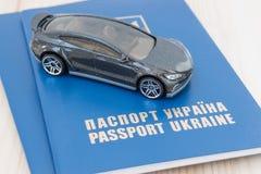 Liten leksakbil överst av Ukraina pass arkivfoto