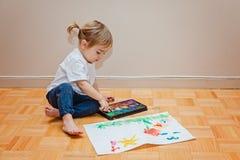 Liten litet barnflicka som försöker att dra med hennes finger Målarfärger papper som är idérikt Arkivfoto