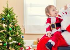Liten litet barnflicka som talar till Santa Claus Royaltyfria Bilder