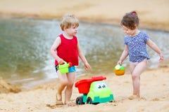 Liten litet barnpojke och flicka som spelar samman med sandleksaker Arkivbild