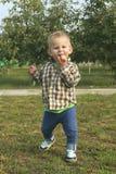 Liten litet barnpojke som äter röda äpplen i fruktträdgård royaltyfri foto