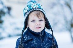 Liten litet barnpojke som har gyckel med snö utomhus på härliga wi Arkivbilder