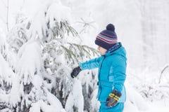 Liten litet barnpojke som har gyckel med snö utomhus på härliga wi Royaltyfri Bild