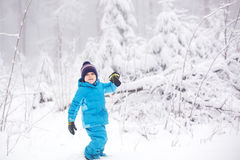 Liten litet barnpojke som har gyckel med snö utomhus på härliga wi Royaltyfria Foton