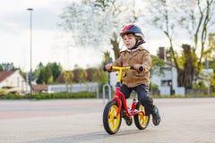 Liten litet barnpojke som har gyckel och rider hans cykel Royaltyfria Bilder