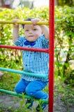 Liten litet barnpojke som har gyckel på en lekplats Royaltyfri Foto