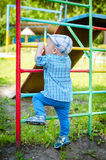 Liten litet barnpojke som har gyckel på en lekplats Royaltyfria Bilder