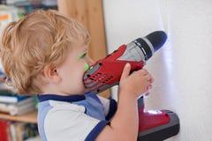 Liten litet barnpojke som leker med den inomhus drillen Royaltyfri Foto