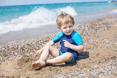 Liten litet barnpojke som spelar med sand och stenar på stranden Royaltyfri Bild