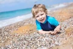 Liten litet barnpojke som spelar med sand och stenar på stranden Royaltyfria Bilder