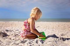 Liten litet barnunge som spelar på stranden som bygger en sandslott arkivbild