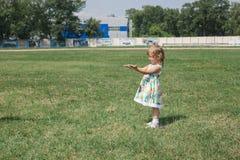 Liten lockig blond flicka som utomhus spelar Royaltyfri Foto