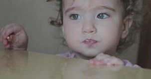 Liten lockig flicka som äter sugrörbagerit arkivfilmer