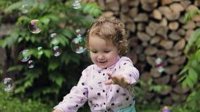 Liten lockig flicka som spelar med såpbubblor som känner sig lyckliga långsam rörelse Bubblashow lager videofilmer