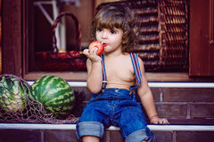 Liten lockig haired pojke med äpplet royaltyfria foton
