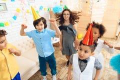 Liten lycklig barndans på födelsedagpartiet Små barn på födelsedagberömmar Royaltyfri Bild