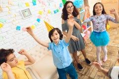 Liten lycklig barndans på födelsedagpartiet Små barn på födelsedagberömmar arkivbild