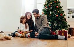 Liten lycklig familj som hemma firar jul arkivbild
