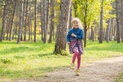Liten lycklig flicka med ett leende på hennes framsida som utomhus hoppar och spelar royaltyfri foto