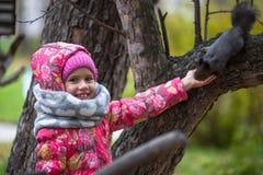 Liten lycklig flicka med handen som matar en ekorre i parkera Arkivbild