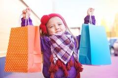 Liten lycklig flicka med köp i händer fotografering för bildbyråer