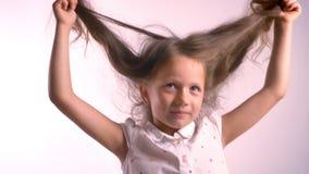 Liten lycklig flicka som rymmer hennes långa hår och lyfter det och att stå i studio med rosa bakgrund som ler stock video