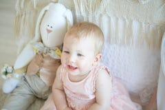 Liten lycklig flicka som sitter nära säng med leksakkanin arkivfoton