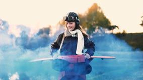 Liten lycklig flygareflicka som kör och rotera i rolig pappnivå med blå färgrök som spelar en pilot- ultrarapid lager videofilmer