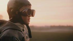 Liten lycklig pojke i den roliga gamla pilot- dräkten som bär retro flygexponeringsglas som gör enfaldiga framsidor i solnedgångf arkivfilmer