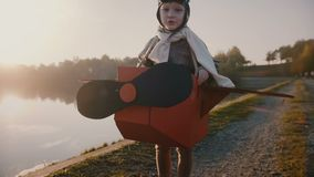 Liten lycklig pojke i rolig plan pilot- dräkt som föreställer för att vara en flygare på fantastisk ultrarapid för sjö för höstso arkivfilmer