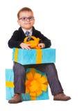 Liten lycklig pojke i spectecles med den stora presenten Royaltyfria Foton