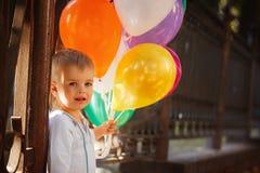 Liten lycklig pojke med färgrika ballonger som är utomhus- i sommar Fotografering för Bildbyråer