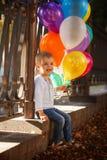 Liten lycklig pojke med färgrika ballonger som är utomhus- i sommar Arkivbilder