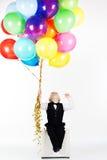 Liten lycklig pojke som rymmer färgrika ballonger Arkivfoton