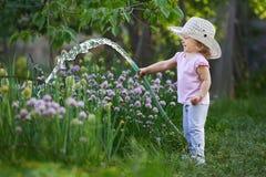 Liten lycklig trädgårdsmästare som bevattnar lökar