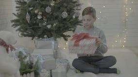 Liten lycklig upphetsad ask för gåva för gåva för pojkeöppningsjul i dekorerat rum för atmosfär för träd för nytt år festligt stock video