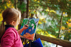 Liten målare på arbete nära vattenfallet Arkivbild
