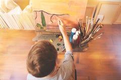 Liten målare som arbetar i konststudio Arkivfoto