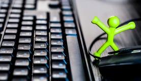 Liten man nära den datortangentbordet och musen Arkivfoto