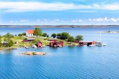 Liten by med röda byggnader i den finlandssvenska skärgården Royaltyfria Foton