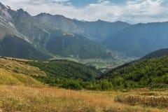 Liten by mellan berg Arkivfoto