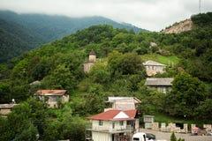 Liten by mellan bergen i Armenien Arkivbilder