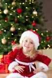 Liten miss santa som framme ler av julträdet arkivbilder