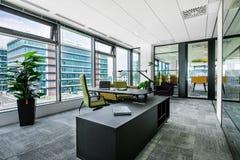 Liten modern kontorsstyrelse- och mötesruminre med skrivbord, stolar och cityscapesikt royaltyfri fotografi