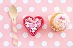 Liten muffin med rosa glasyr på kaka Royaltyfri Foto