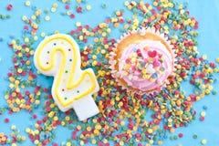 Liten muffin med rosa glasyr på kaka Royaltyfria Foton