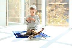 Liten muslimsk pojke med misbaha och Koranen som ber på filten arkivbild