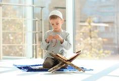 Liten muslimsk pojke med misbaha och Koranen som ber på filten royaltyfri foto