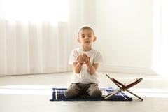 Liten muslimsk pojke med misbaha och Koranen som ber på filten royaltyfria bilder